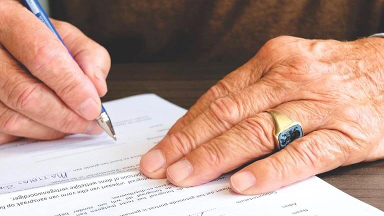 Image of man signing a South Florida Estate Planning Document with Estate Planning Attorney Boca Raton, ASR Law Firm.