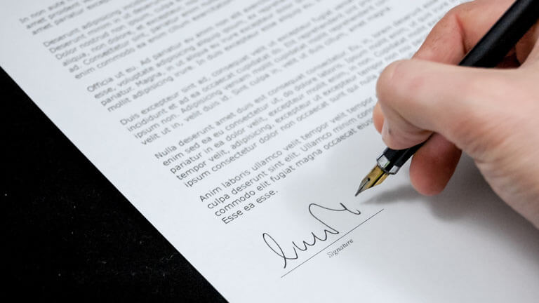 An image of a person signing a real estate contract that illustrates the comprehensive real estate conveyance solutions at ASR Law Firm.