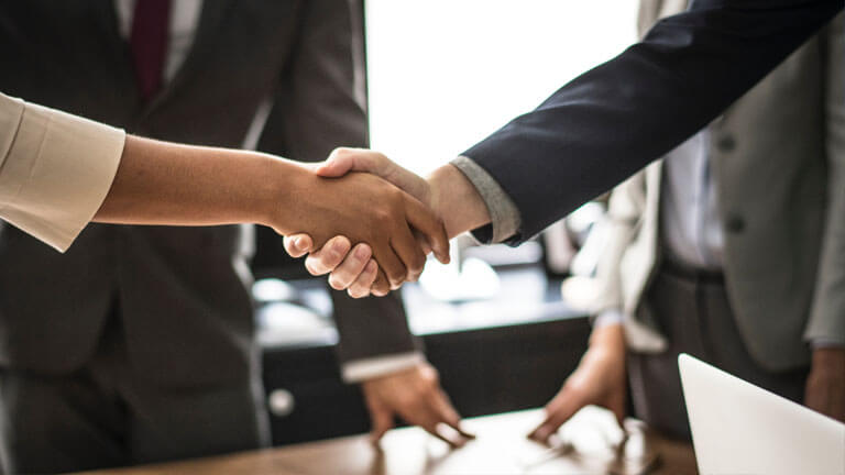 An image of a two people shaking hands that illustrates the comprehensive real estate title and closing services available at ASR Law Firm.