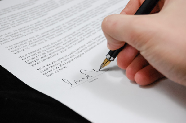 An image of someone signing a document to illustrate the ability to order title insurance through ASR Law Firm.
