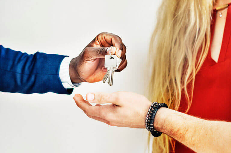 An image of a realtor handing the keys to a newly purchased home to a home buyer that represents the comprehensive boca raton title company and title insurance services of ASR Law Firm.