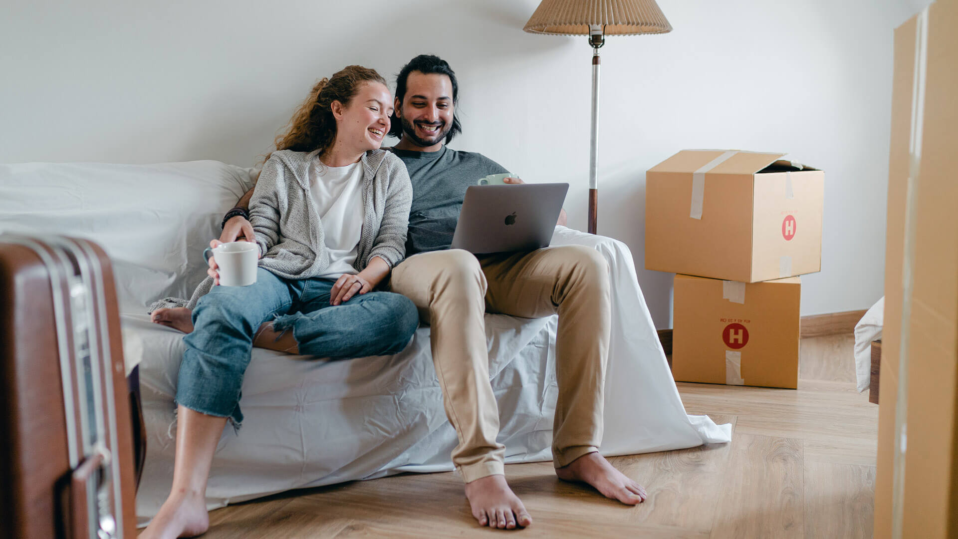 An image of a couple on a couch looking at common closing costs in Florida for buyers of real estate.
