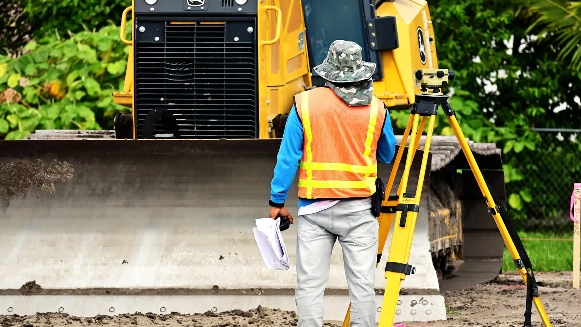 An image of a surveyor doing an ALTA survey on a piece of property with construction equipment in the background.